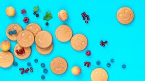 Stop motion food background. Delicious mini smile pancakes with berries on blue surface, top view, dynamic scene stock video