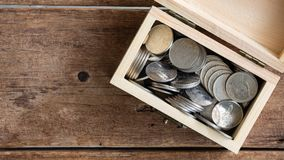 Stop motion footage of silver coins Thai Baht increasing in toy wooden chest on wwod table, top view, 4K, ultra high definition re. Solution, thirty frame per stock video footage