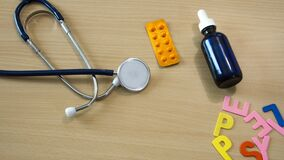 Stop motion time lapse of word with colorful epilepsy letters on a table with a stethoscope and moving medicines