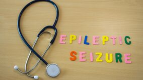 Stop motion time lapse of word with colorful epileptic seizure letters on a table with a stethoscope and moving medicines
