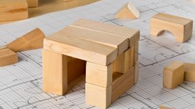 Stop motion timelapse of house built from wooden blocks on architectural building blueprint stock video footage