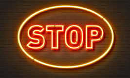 Stop neon sign on brick wall background. Stock Photos