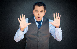 Stop and no. Closeup portrait of young, angry man in vest and blue tie, gesturing no with hands and saying stop with his mouth,  on gray black background Royalty Free Stock Photos