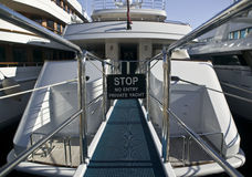 Stop, no entry, private yacht!. Rear of a luxury yacht with footbridge, reling and prohibition sign Royalty Free Stock Image