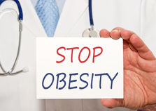 Stop Obesity - doctor holding white sign with text. In his hand royalty free stock photography