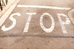 Stop painted on asphalt outdoor Royalty Free Stock Photo