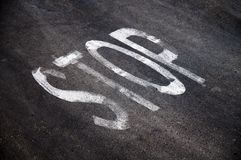 STOP painted on asphalt surface Stock Photography