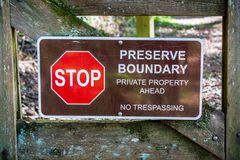 `Stop; Preserve Boundary; Private Boundary Ahead; No trespassing` sign. Posted on a wooden gate stock image