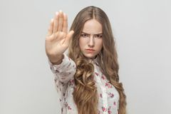 Stop! Rage young woman showing no sign. Studio shot, gray background Stock Photography