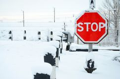 Stop. Red road sign is located on the motorway crossing the railway line in winter season.  Royalty Free Stock Images