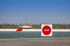 Stop red sign on barrier in a harbor Stock Photography