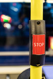 Stop request button for bus. Extreme close up of red stop request button on yellow pole for public bus with obscured seat and window in background royalty free stock photography
