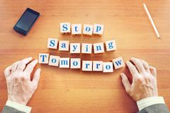 Stop saying tomorrow. Businessman made text from wooden cubes stock images