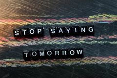 Stop Saying Tomorrow on wooden blocks. Cross processed image with blackboard background.