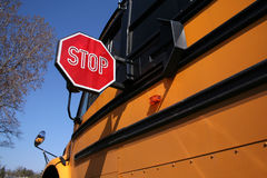 Stop for Schoolbus. Medium view showing side of schoolbus with stop sign extended for approaching traffic. Blue sky and neighborhood tree in background Royalty Free Stock Photos