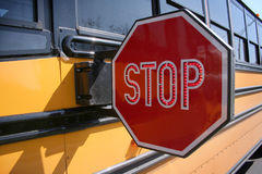 Stop for Schoolbus. Front view, closeup of stop sign extended for approaching traffic with medium view of schoolbus with . Bus receeding in perspective filling Stock Photos