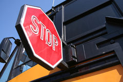 Stop for Schoolbus. Child's view, low perspecitve closeup of stop sign extended for approaching traffic with medium view of schoolbus with . Against blue sky Royalty Free Stock Photography