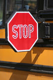 Stop for Schoolbus - Vertical. Closeup of stop sign extended for approaching traffic against view of schoolbus filling frame. Vertical format Royalty Free Stock Images