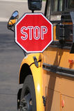Stop for Schoolbus - Vertical. Medium view of stop sign extended for approaching traffic from angle behind schholbus. Paved road ahead of bus in background Stock Photos