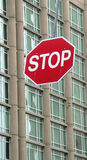 Stop Sign. Bright red stop sign hangs in front of a high rise building Stock Photography