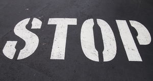 Stop sign. Painted on a asphalt road surface Stock Images