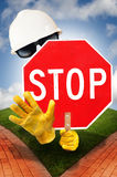 Stop sign. A invisible person with sunglasses a hard hat and gloves holding a scratched stop sign on a road with two directions.  Concept for decision making Royalty Free Stock Photos