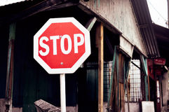 Stop sign against the backdrop of dilapidated housing Stock Photos