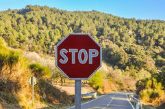 Stop sign in the background of beautiful landscape and road. Royalty Free Stock Images