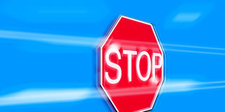 Stop sign in blue sky. Hexagonal red stop with with blue sky and blurred cloudscape background Royalty Free Stock Photos