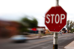 Stop Sign Blurred Traffic. Stop sign with out of focus car and street in the background Stock Image