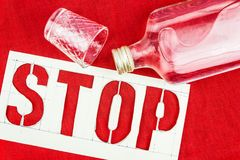 Stop sign, bottle and shot glass on the red tablecloth. The danger of alcoholism. Fight against excessive consumption of alcoholic beverages Stock Image