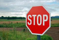 Stop Sign on Country Road. Image of a red stop sign against country road scenery stock photo