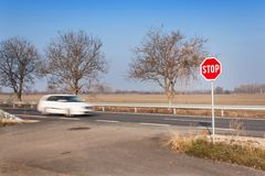 Stop Sign at Crossroads. Rural road. Exit onto the main road. Main road. Dangerous road. Traffic signs stop. Stop Sign at Crossroads. Rural road. Exit onto the Royalty Free Stock Photos