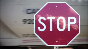 Stop Sign Detail at Train Crossing. A red stop sign at a railroad crossing while a cargo train passes behind. With audio stock video