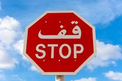 Stop sign in English and Arabic with blue sky and clouds in background. royalty free stock photography
