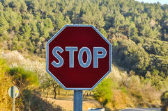 Stop sign with forested mountain in the background. Royalty Free Stock Image