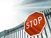 Stop sign on the gate. In sun rays Royalty Free Stock Photo