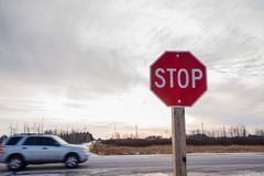 Stop Sign at an Intersection along a Highway at Sunset. Stop Sign at an Intersection along a Highway in the Countryside of Ontario at Sunset with a Passing Car Stock Photography