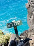 STOP Sign. With ocean sea back drop on rocks cliff edge Royalty Free Stock Photography