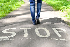 Stop sign painted on the road and female legs. Stop sign painted on the road and female legs next to the sign Royalty Free Stock Photo