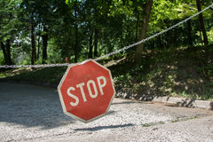 Stop sign at park. Red-white , hanging on metal rod. In the background is forest stock photos