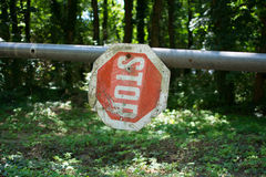 Stop sign at park. Red-white , hanging on metal rod upside down. In the background is forest royalty free stock images