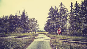 Stop sign at railway crossing in a rural landscape. Stock Image