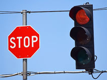 Stop sign and red light at the road crossing Royalty Free Stock Photos