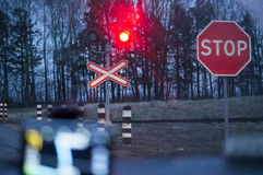 Stop sign and red traffic lights at a railway crossing Royalty Free Stock Photography