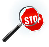 Stop Sign under magnifying glass Royalty Free Stock Images