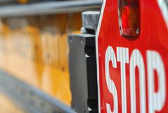 Stop sign on a yellow school bus. The colorful juxtaposition of the yellow bus with the red sign, indicating the crossing of children across a street to school royalty free stock photo