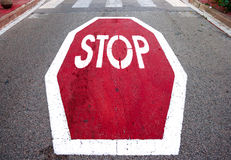 Stop signal on asphalt. Red and big stop signal on grey asphalt Stock Image