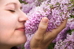 Stop and Smell the Lilacs. A lady enjoying the smell of some lilacs Royalty Free Stock Images