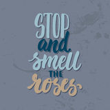 Stop and smell the roses - hand drawn lettering phrase  on the grey grunge background. Fun brush ink inscription Royalty Free Stock Images